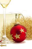 Red christmas ball near glass with champagne, angels hair in front of a cha — Stock Photo