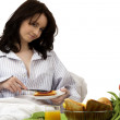 Young woman with breakfast in bed — Stock Photo