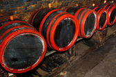Wine barrels stacked in the old cellar of the winery — Stock Photo