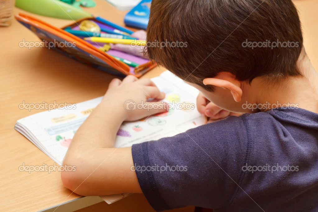 Boy doing homework  with color pencil, painting fruits — Stock Photo #4490725