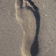 Imprint of human feet in the sand on the beach — Stock Photo