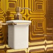 Stock Photo: Luxury pump soap bottle without in bathroom. Gold background.