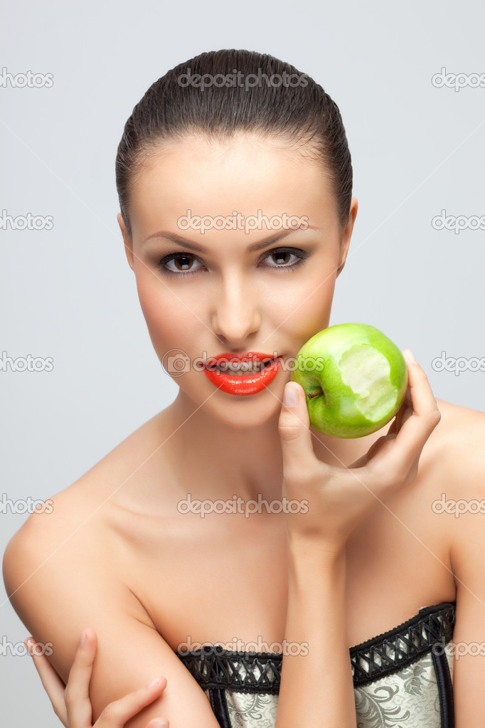 A portrait of a slinky hot girl holding a bitten green apple in her hand.  Stock Photo #3994408