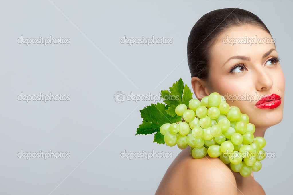 A pretty sexy lady with a bunch of grape of her nude shoulder looking aside.  Stock Photo #4017503