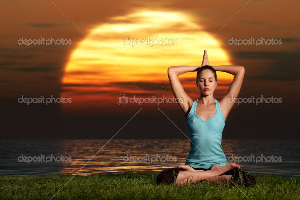 A sportive beautiful woman training yoga on the beach at dawn. — Stock Photo #4453872