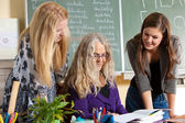 Female teacher and students — Stock Photo