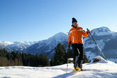 A woman makes a snowshoe tour in a beautiful mountain landscape. — Stock Photo