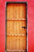 Wooden door as red wall — Stock Photo
