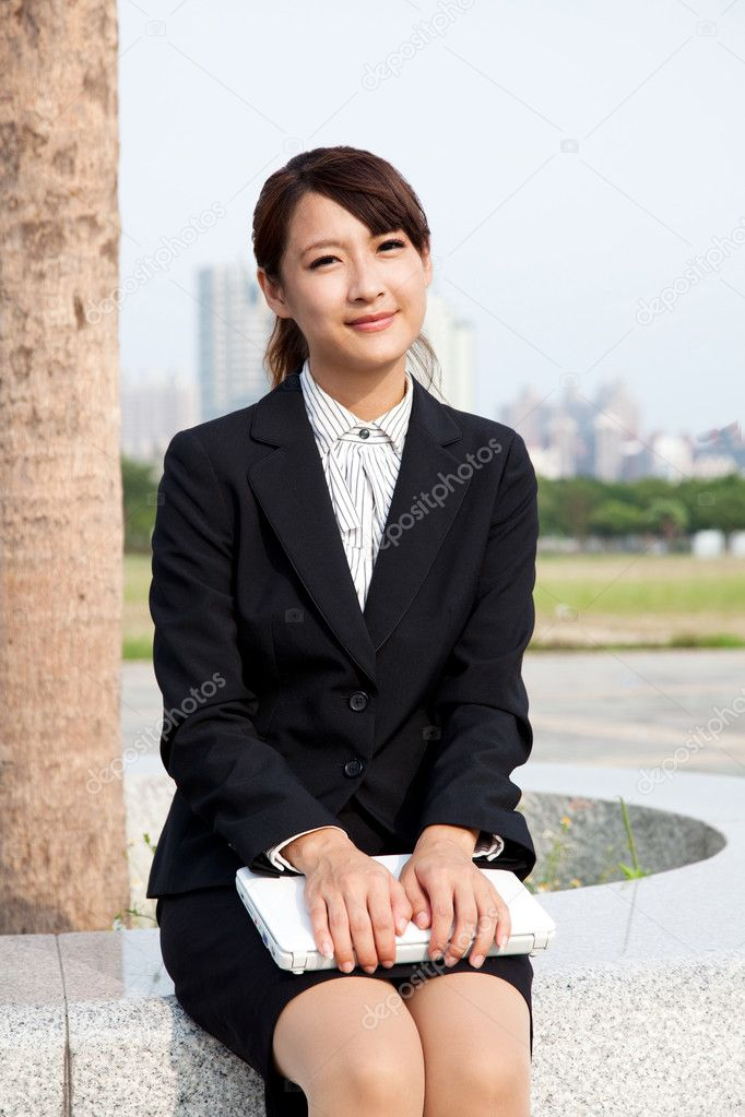 Young and smiling businesswoman  holding a laptop  Stock Photo #4131372