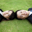 Young adult couple and lay on the grass — Stockfoto
