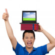 Young man gives his thumbs up with book and laptop - Stock Photo
