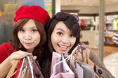 Happy girls in a shopping mall — Stock Photo