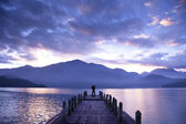 Man stand on a pier and watching the mountains and lake — Stock Photo