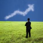 Бизнесмен стоять на лугу и смотреть бизнес прибыль граф clo — Стоковое фото