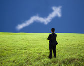 Businessman stand in the meadow and watch the business profit graph of clo — Stock Photo
