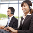Smiling customer service representative in modern office with a headset - Stock Photo