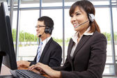 Smiling customer service representative in modern office with a headset — Stock Photo