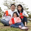 Chinese family holding red envelop — Stock Photo