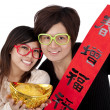 Chinese new year. Young couple holding gold ingot and red spring couplets — Stock Photo