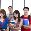 Young smiling students stand in the classroom — Stock Photo