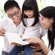 Happy asian family studing together. Parent helping daughter  reading book - Stock Photo