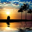 The silhouette of couple watching sunset on the beach — Stock fotografie