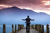 Businessman stand on the pier and watching the mountain and cloud of sunri — Stok fotoğraf