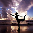 Yoga woman on the beautiful beach at sunrise — Stock Photo