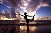 Mulher de ioga na bela praia ao nascer do sol — Foto Stock