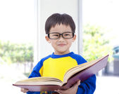 Asian kid smiling and holding book — Stock Photo
