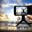 Camera mobile phone and happy jumping man on the beach at beautiful sunrise — Stock Photo