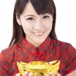 Beautiful asian woman wear cheongsam and holding chinese gold ingot — Stock Photo