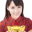 Beautiful asian woman wear cheongsam and holding chinese gold ingot — Stock Photo #5216357