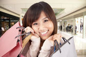 Happy asian woman in a shopping mall — Stock Photo