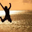 Happy Young man jumping on the beach at sunset — ストック写真