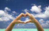 Ruční formování srdce na tropické pláži pozadí — Stock fotografie