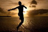 Sylwetka chłopaka, skacząc do morza na zachód słońca — Zdjęcie stockowe