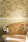Part of vintage chair with flowers standing near the wall — Stock Photo