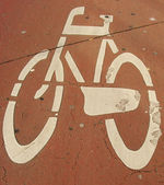 Embossed through many layers of paint bicycle sign on pavement — Stock Photo