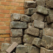 Large stack of cobbles in front of brick wall — Stock Photo #3977042