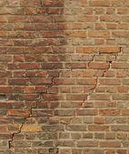 Worn orange brick wall with 2 large cracks — Stockfoto