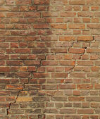 Worn orange brick wall with 2 large cracks — Stock Photo