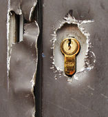 Vandalized gray door with lock — Stock Photo
