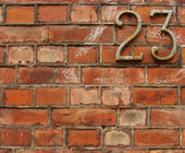 Rusty metal number 23 twenty three attached to a brick wall — Stock Photo