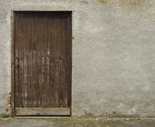 Vecchia porta di legno marrone, incastonato in una parete di cemento grigia — Foto Stock