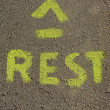 The word rest painted in yellow on pavement - Stock Photo