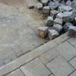 Stack of cobbles laying on pavement and sidewalk — Stock fotografie