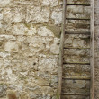 Vintage wooden ladder in front of an old stone wall - Stock Photo