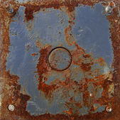 Blue colored rusty metal plate with circular shape in the middle — Stock Photo
