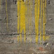 Stock Photo: Dirty gary industrial concrete wall with fat yellow paint drips